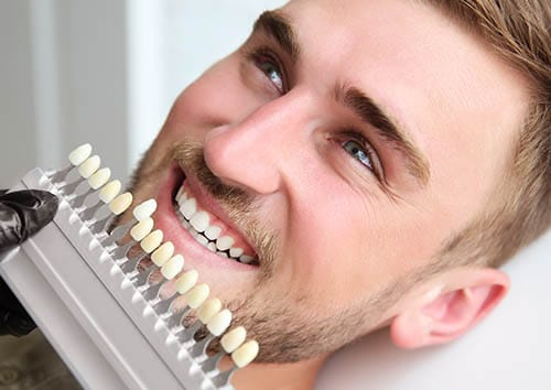 man choosing tooth color for dental bonding
