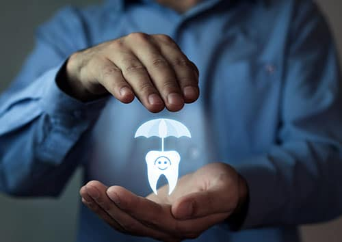 image of a man's hands holding a tooth with an umbrella representing dental benefits membership