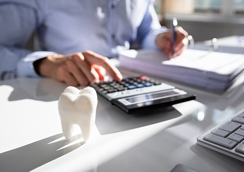 person using calculator to compute dental insurance benefits